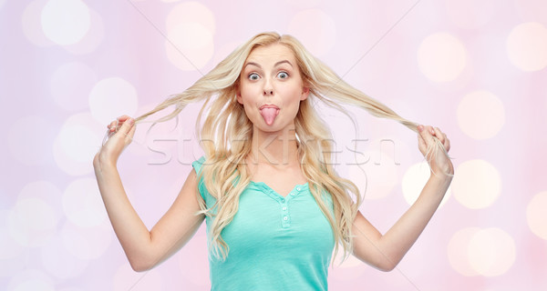 happy young woman showing tongue and holding hair Stock photo © dolgachov
