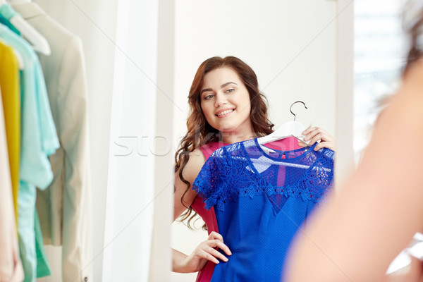happy plus size woman with dress at mirror Stock photo © dolgachov