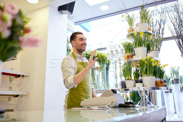 florist man or seller at flower shop counter Stock photo © dolgachov