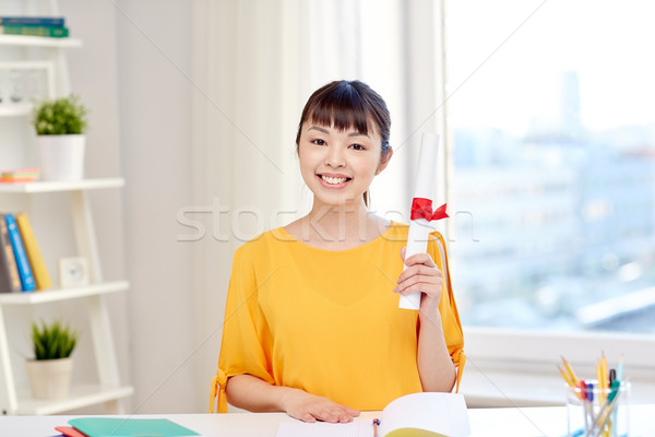 Stock photo: happy asian woman student with diploma at home