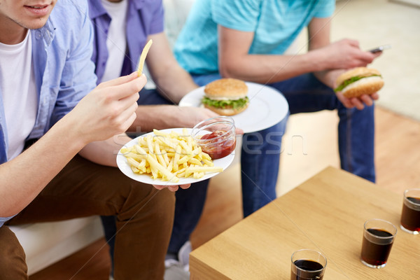 close up of friends eating fast food at home Stock photo © dolgachov