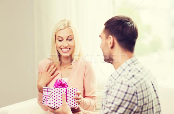 happy man giving woman gift box at home Stock photo © dolgachov