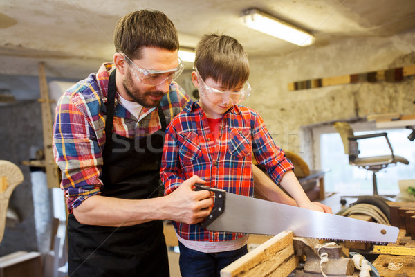 father and son with saw working at workshop Stock photo © dolgachov