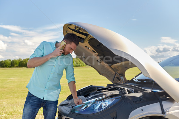 man with broken car calling on smartphone Stock photo © dolgachov
