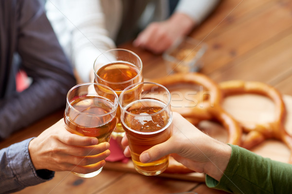 close up of hands clinking beer at bar or pub Stock photo © dolgachov