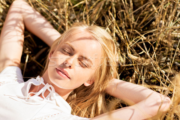 happy young woman lying on cereal field or hay Stock photo © dolgachov