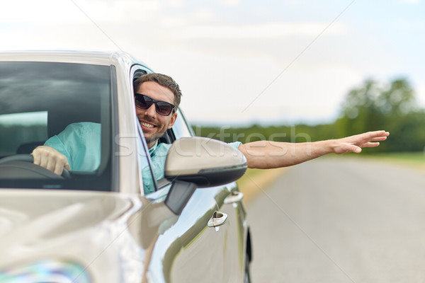 happy man in shades driving car and waving hand Stock photo © dolgachov