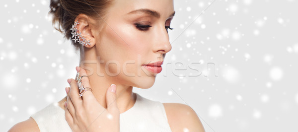 Stock photo: close up of woman in white with diamond jewelry