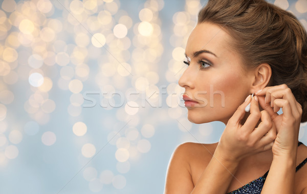 close up of woman woman fastening diamond earring Stock photo © dolgachov