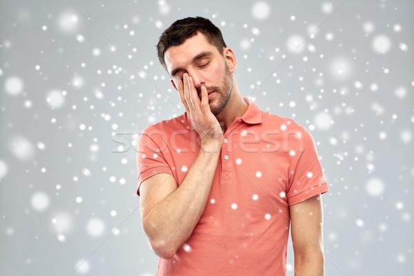 tired sleepy man over snow Stock photo © dolgachov
