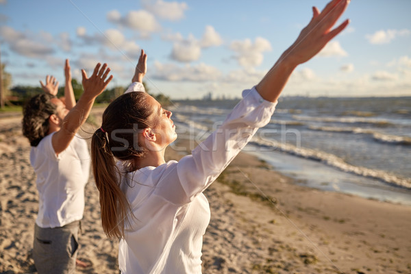 group of people making yoga or meditating on beach Stock photo © dolgachov
