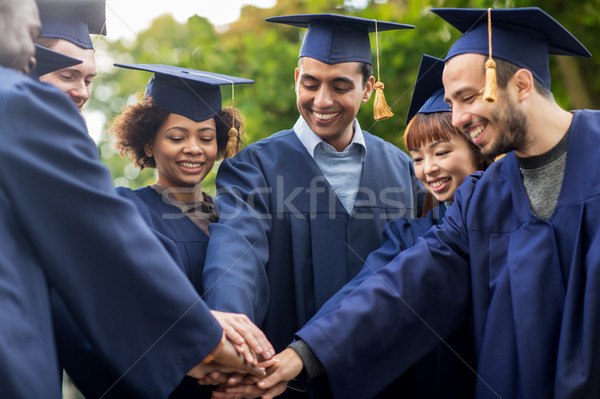 happy students in mortar boards with hands on top Stock photo © dolgachov