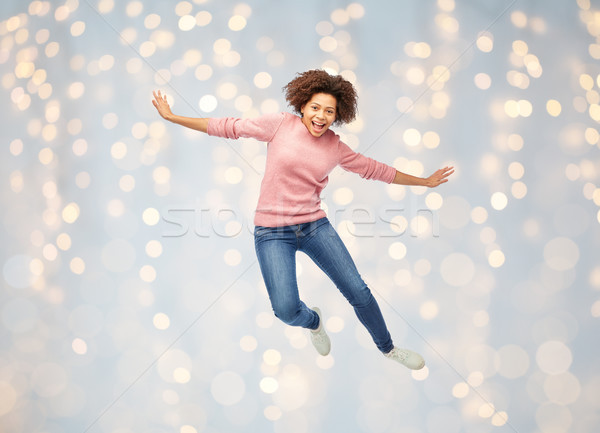 happy african american woman jumping over white Stock photo © dolgachov