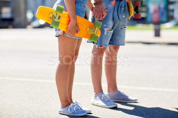 Stock photo: close up of young couple with skateboards in city