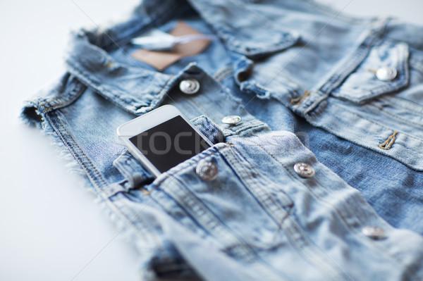 smartphone in pocket of denim jacket or waistcoat Stock photo © dolgachov