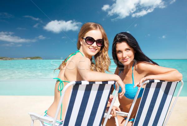 Gelukkig vrouwen zonnebaden stoelen zomer strand Stockfoto © dolgachov
