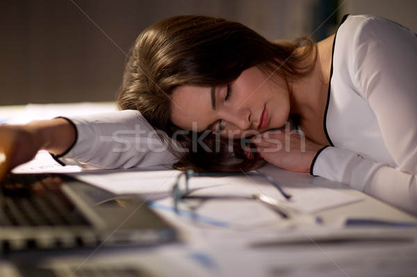 tired woman sleeping on office table at night Stock photo © dolgachov