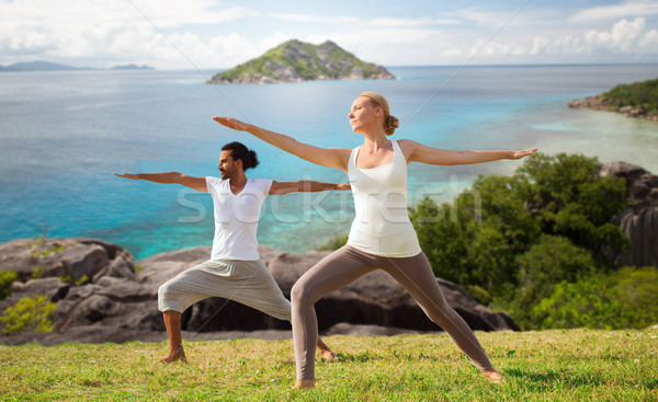 couple making yoga in warrior pose at seaside Stock photo © dolgachov