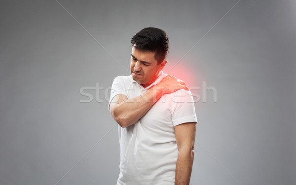 unhappy man suffering from pain in shoulder Stock photo © dolgachov