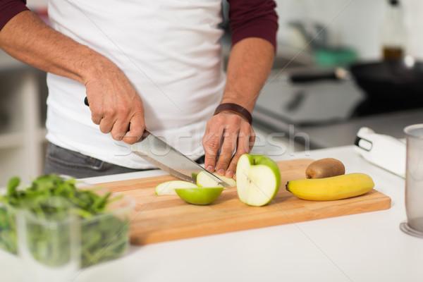 man chopping fruits and cooking at home kitchen Stock photo © dolgachov