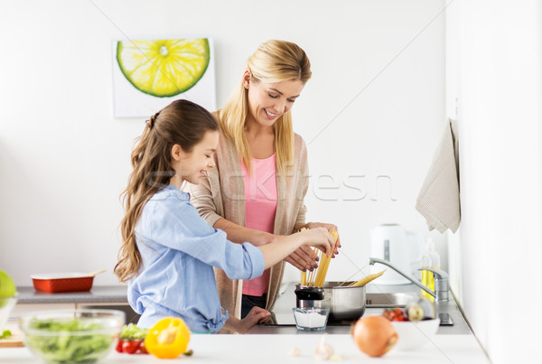 happy family cooking food at home kitchen Stock photo © dolgachov