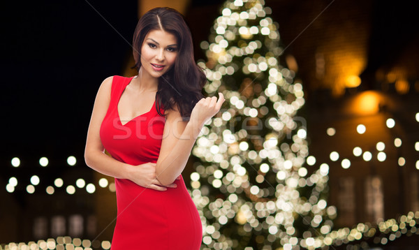 beautiful woman in red dress over christmas tree Stock photo © dolgachov