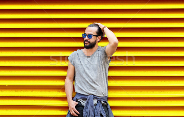 man in sunglasses over ribbed yellow background Stock photo © dolgachov