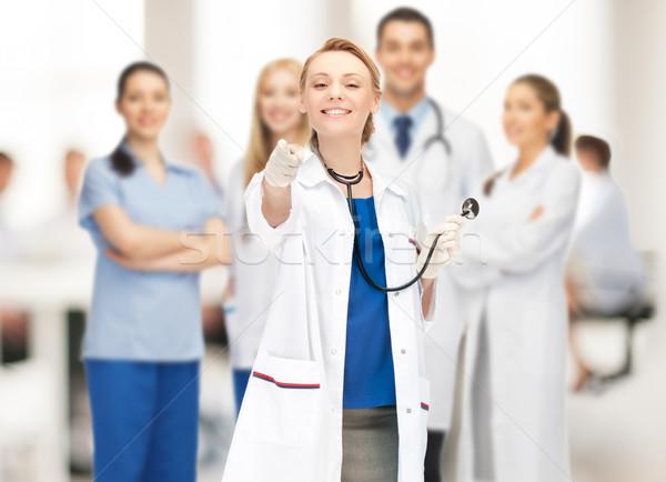Привлекательная женщина врач указывая пальца фотография стороны Сток-фото © dolgachov