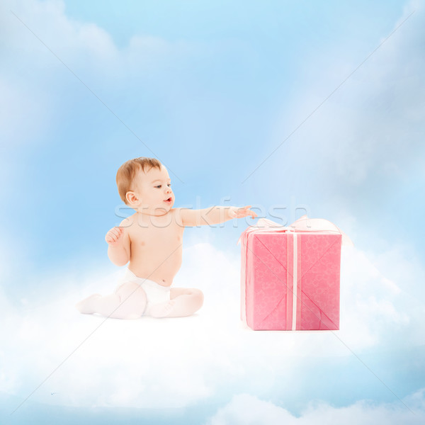 smiling baby with present on the cloud Stock photo © dolgachov