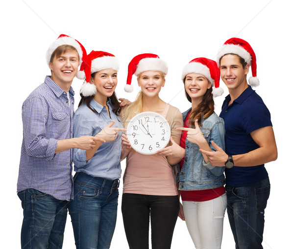 group of smiling students with clock showing 12 Stock photo © dolgachov