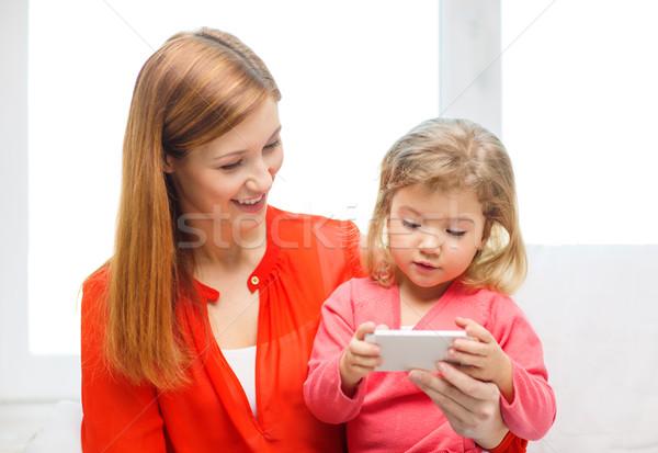 Boldog anya lánygyermek okostelefon otthon család Stock fotó © dolgachov