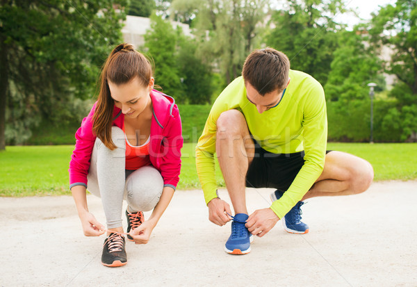 Stock photo: smiling couple tying shoelaces outdoors