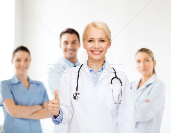 Glimlachend vrouwelijke arts tonen gezondheidszorg Stockfoto © dolgachov