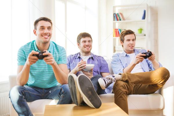 Сток-фото: улыбаясь · друзей · играет · Видеоигры · домой · дружбы