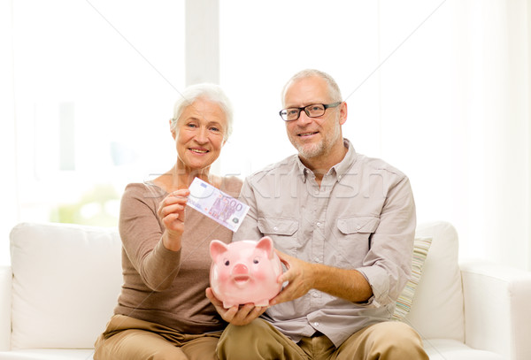 senior couple with money and piggy bank at home Stock photo © dolgachov