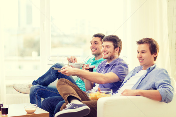 Souriant amis télécommande maison amitié technologie Photo stock © dolgachov