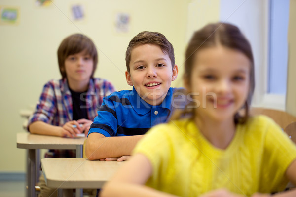 group of school kids with notebooks in classroom Stock photo © dolgachov