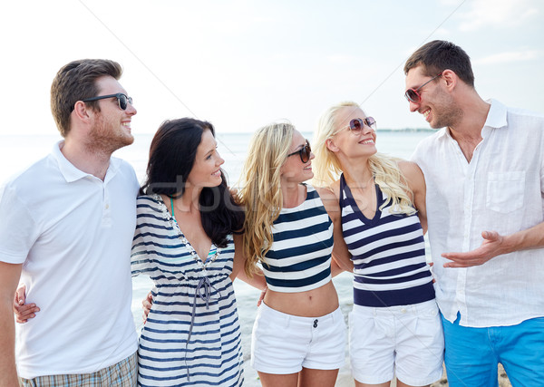 smiling friends in sunglasses talking on beach Stock photo © dolgachov