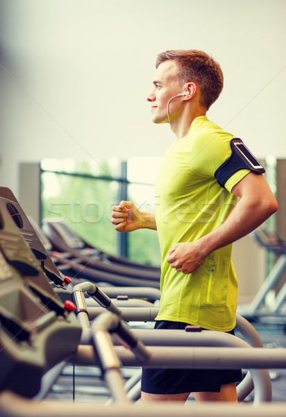 smiling man exercising on treadmill in gym Stock photo © dolgachov