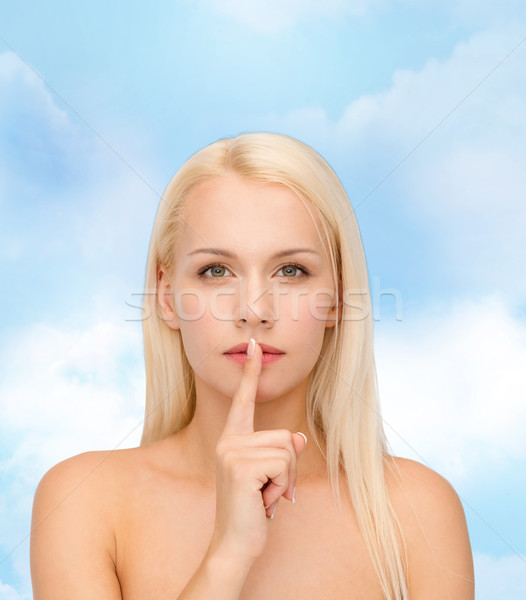 calm young woman with finger on lips Stock photo © dolgachov