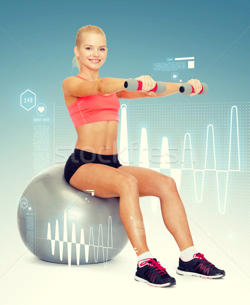 Stock photo: woman with dumbbells sitting on fitness ball