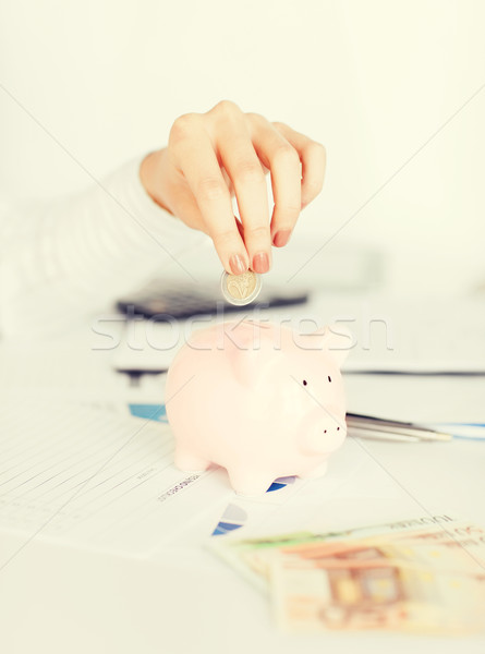 woman hand putting coin into small piggy bank Stock photo © dolgachov