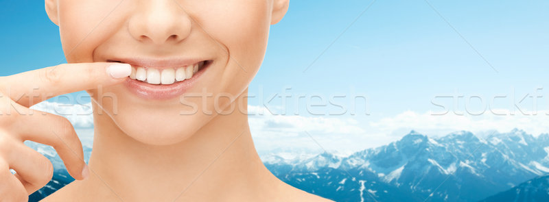 close up of smiling woman face pointing to teeth Stock photo © dolgachov