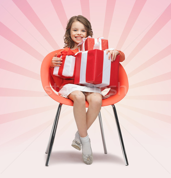 happy little girl with gift boxes sitting on chair Stock photo © dolgachov