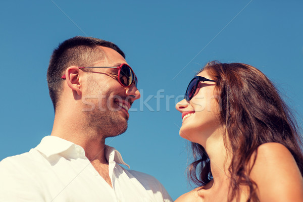 smiling couple over blue sky background Stock photo © dolgachov