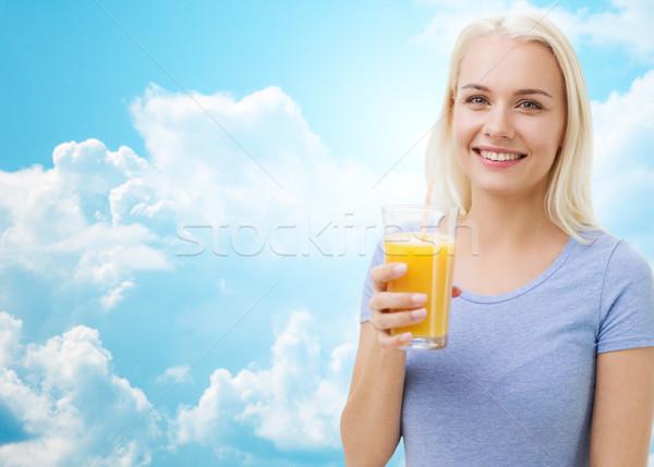 smiling woman drinking orange juice over sky Stock photo © dolgachov