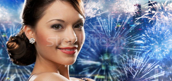 happy woman with diamond earring over firework Stock photo © dolgachov