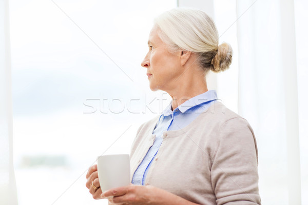 lonely senior woman with cup of tea or coffee Stock photo © dolgachov