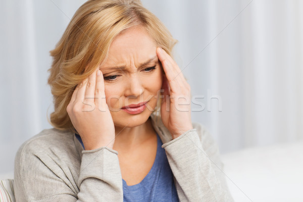 Stock photo: unhappy woman suffering from headache at home