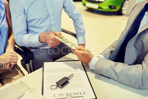 customers giving money to car dealer in auto salon Stock photo © dolgachov